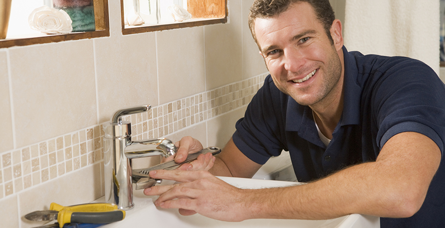 man fixing sink