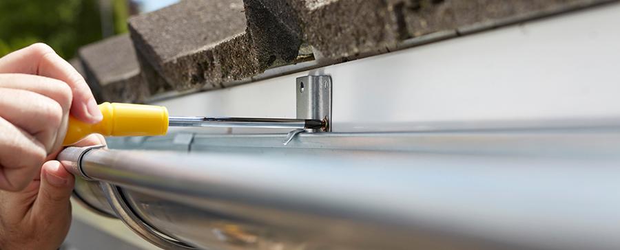 Man installing gutters on roof