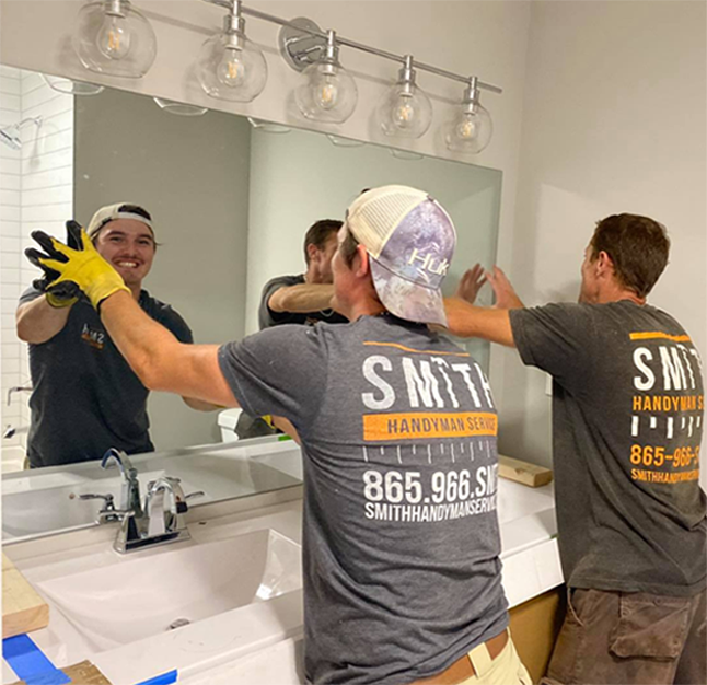 Two men putting up a mirror in a bathroom