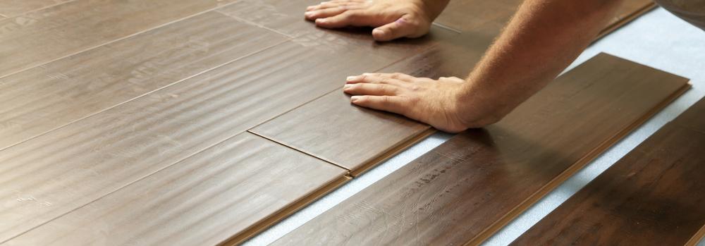 Person installing brown flooring in room
