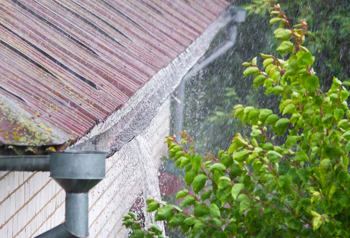 Water overflowing a sagging gutter in a rainstorm