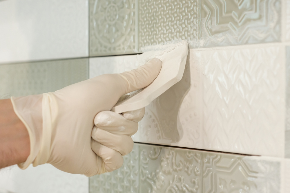 Close-up of a person grouting a tile