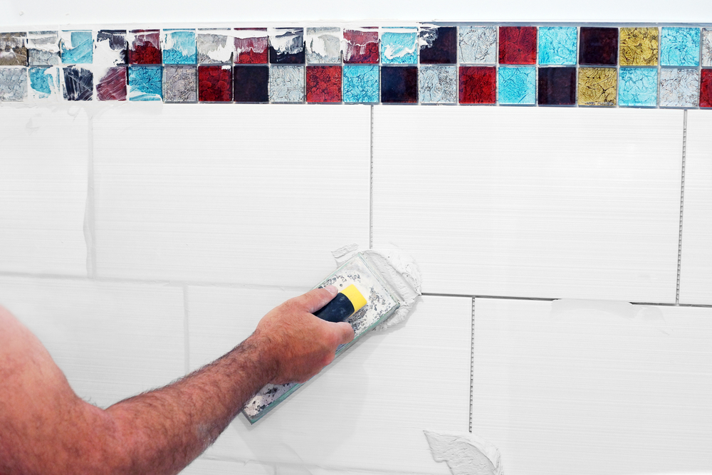 Close-up of a man correctly grouting multi-colored tiles