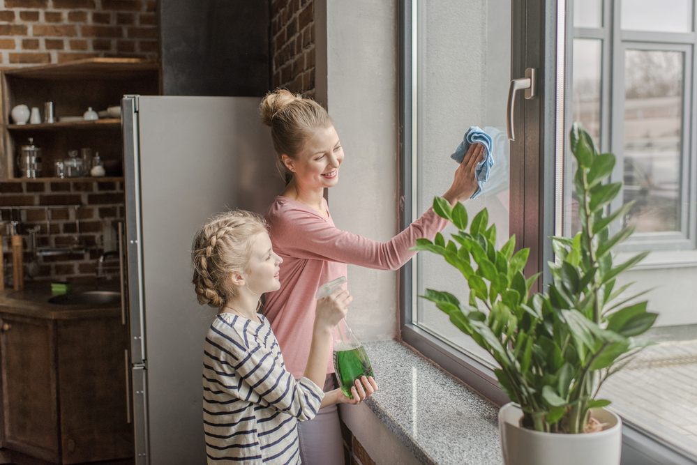 Mother and daughter cleaning a window