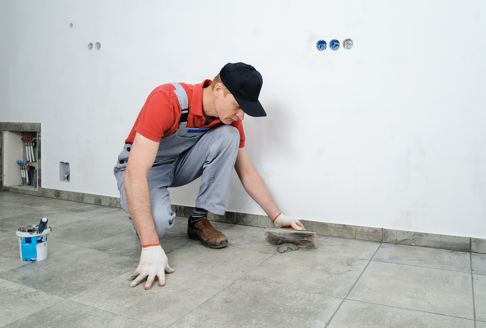 Worker grouting ceramic tiles